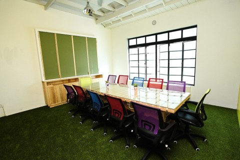 Our conference room table is constructed out of recycled pallets as is the projector screen/chalkboard/cupboard. A whiteboard was not incorporated, as markers are not environmentally friendly.