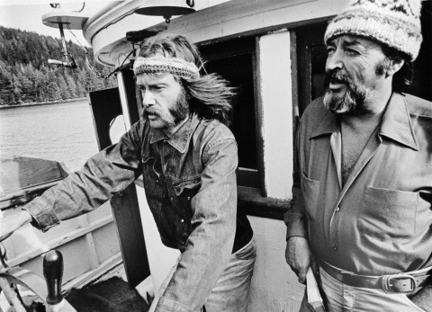 Bob Hunter on left at the helm of the Phyllis Cormack together with Ben Metcalfe. En route to Amchitka.    (Greenpeace Witness book page 94)  (The Greenpeace story book page 12 similar).